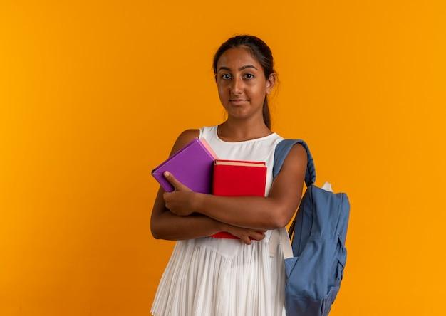 Complacido joven colegiala con mochila sosteniendo libros