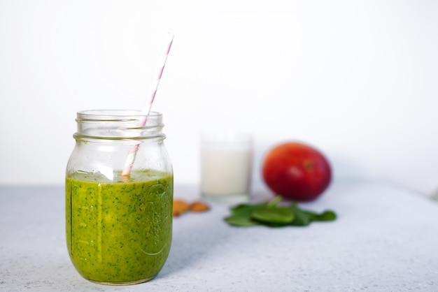 Componentes de un batido saludable de vitaminas green reach con espinacas, mango, leche de almendras y fresa