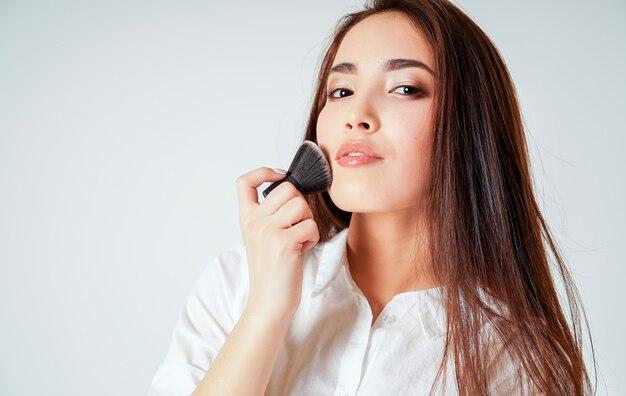 Componga el cepillo kabuki en la mano de la mujer joven asiática sonriente con el pelo largo oscuro en blanco