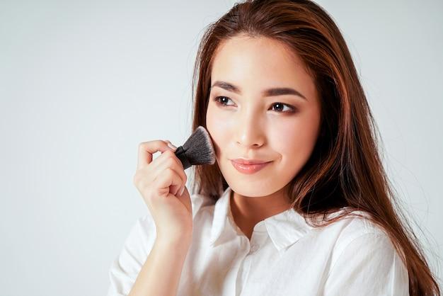 Componga el cepillo kabuki en la mano de la sonriente joven asiática con cabello largo y oscuro