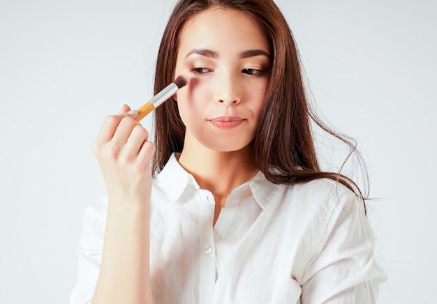 Componga el cepillo en la mano de la mujer joven asiática sonriente con el pelo largo oscuro en el ackground blanco