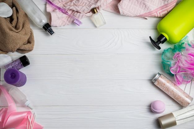 Composición con los accesorios del baño toalla gel de ducha toallita cepillo de dientes sobre fondo de madera blanco con copyspace