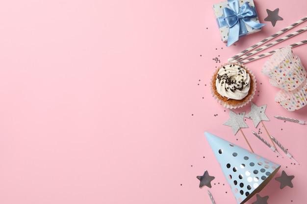 Composición con accesorios de cupcake y cumpleaños sobre fondo rosa, espacio para texto