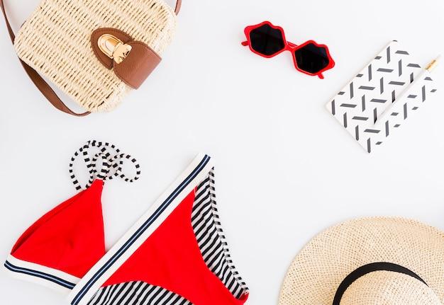 Composición de los accesorios de playa de vacaciones tropicales sobre fondo blanco