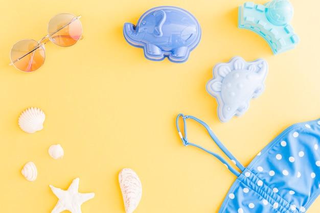 Composición con accesorios de playa de verano de vacaciones sobre fondo amarillo