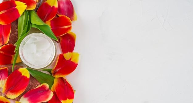 Composición con aceite de coco en un frasco en blanco rodeado de pétalos de tulipán, vista superior con espacio de copia