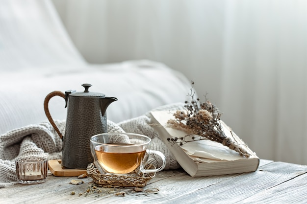 Composición acogedora con una taza de té y un libro en el interior de la habitación sobre un fondo borroso.