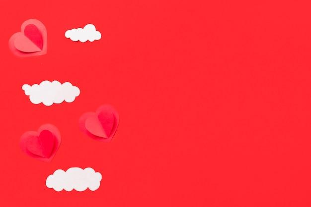 Composición de adornos de papel corazones y nubes.