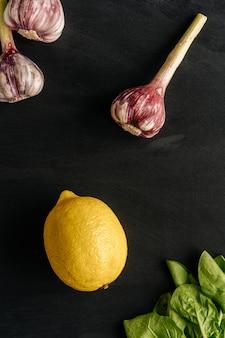 Composición de ajo y limón sobre un fondo negro con hierbas frescas