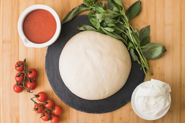 Composición con albahaca orgánica fresca verde e ingredientes para pizza sobre fondo de madera