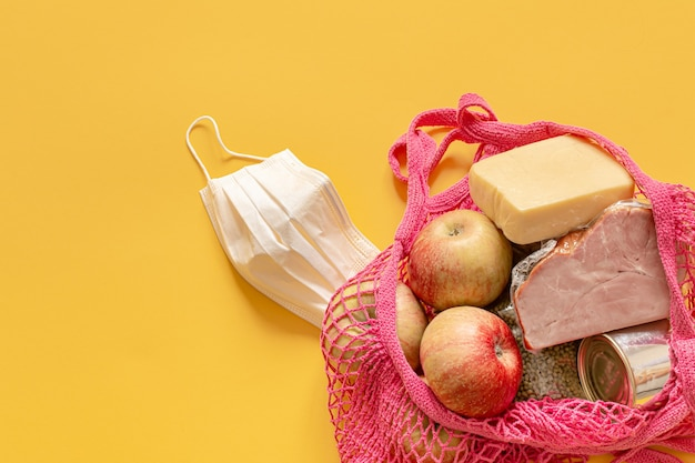 Composición de los alimentos en una bolsa de hilo de cerca. donaciones de alimentos o el concepto de entrega de alimentos durante la cuarentena.