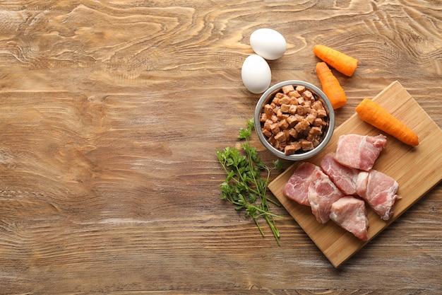 Composición con alimentos para mascotas y diferentes productos en mesa de madera.