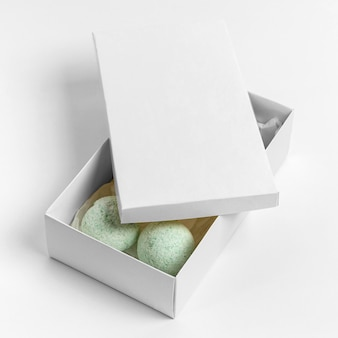 Composición de alto ángulo de bombas de baño verdes en caja sobre fondo blanco.