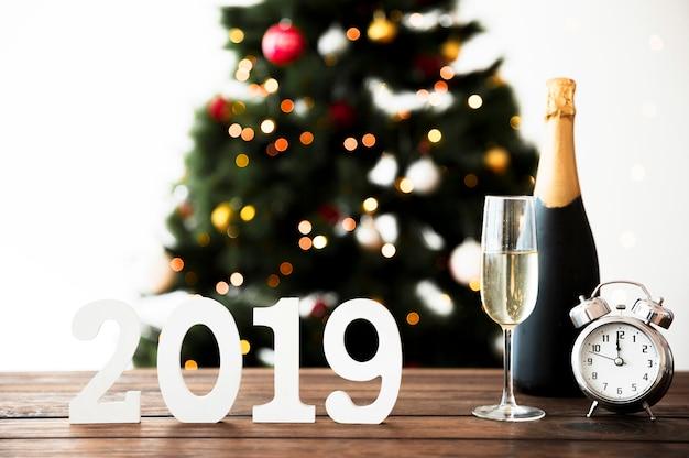 Composición de año nuevo con botella de champán y reloj en mesa