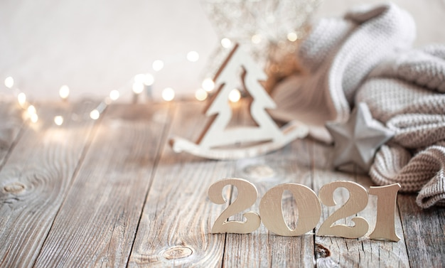 Composición de año nuevo festivo con número de año nuevo de madera sobre un fondo borroso claro con decoración navideña.