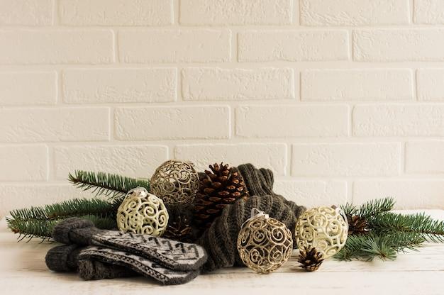 Composición de año nuevo en el fondo de una pared de ladrillo blanco. mitones y bufanda de punto, originales bolas navideñas, ramas y un gran cono.