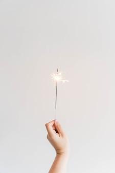 Composición de año nuevo con mano sujetando bengala
