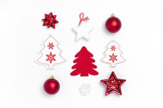 Composición de año nuevo y navidad de bolas rojas, estrellas blancas, árbol de navidad, ciervos sobre papel blanco.