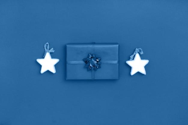 Composición de año nuevo y navidad de estrellas blancas, caja de regalo sobre fondo azul. color de moda del año 2020. vista superior, plano, copia espacio