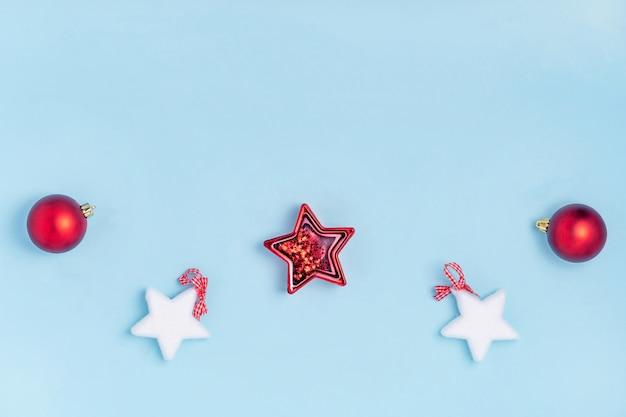 Composición de año nuevo y navidad. juguetes de navidad rojo y blanco - estrellas, bolas de navidad sobre fondo de papel azul pastel. vista superior, plano, copia espacio