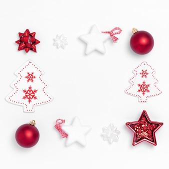 Composición de año nuevo y navidad. marco de bolas rojas, estrellas blancas, árbol de navidad, ciervos sobre papel blanco.