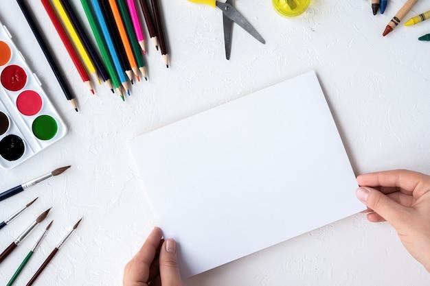 Composición de aparatos de pintura. lápices, rotuladores, pinceles, pinturas y papel. fondo claro