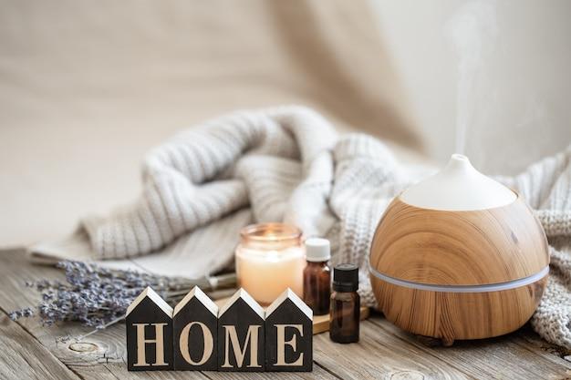 Composición aromática con difusor de aceite aromático moderno sobre superficie de madera con elemento tejido, aceites y vela