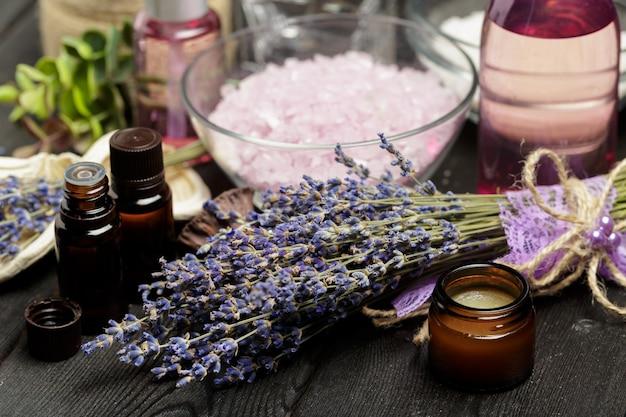 Composición aromática de lavanda, hierbas, cosméticos y sal en una mesa oscura.