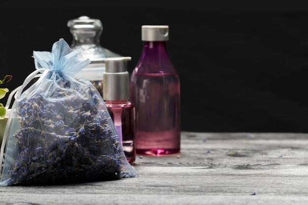 Composición aromática de lavanda, hierbas, cosméticos y sal sobre una mesa oscura