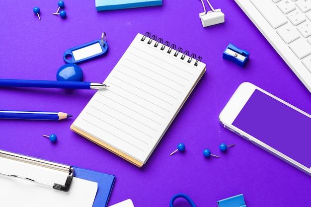 Composición de artículos de estilo de vida de oficina en púrpura, suministros de oficina de teclado de computadora en el escritorio en la oficina