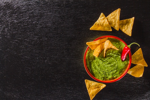 Composición artística con guacamole y nachos
