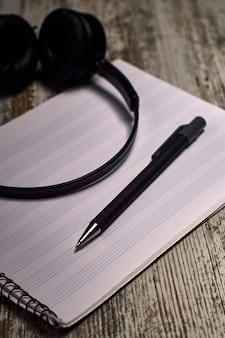 Composición de los auriculares negros al lado de un cuaderno de pentagrama vacío en una mesa de madera