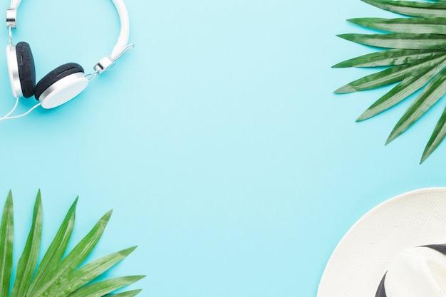 Composición de auriculares planta hojas y sombrero.