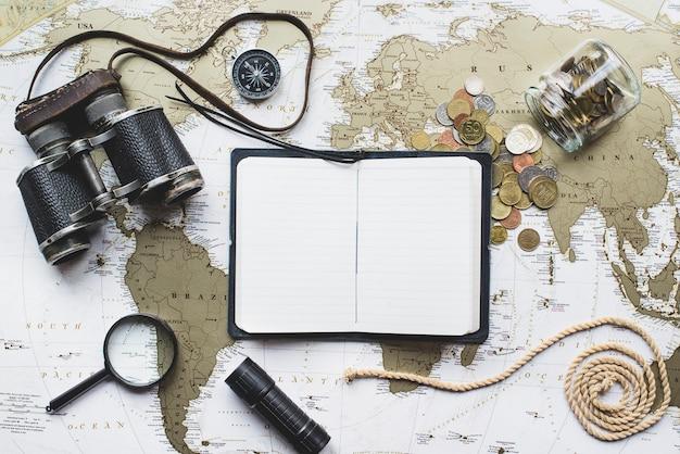 Composición de aventura con mapa del mundo y cuaderno abierto