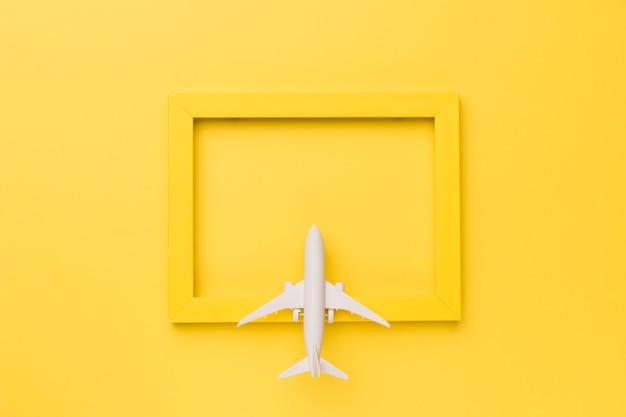 Composición de avión de juguete en marco amarillo