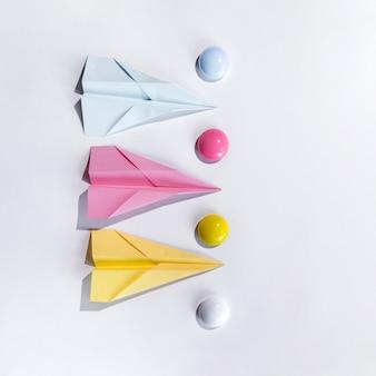Composición con avión de papel sobre mesa.