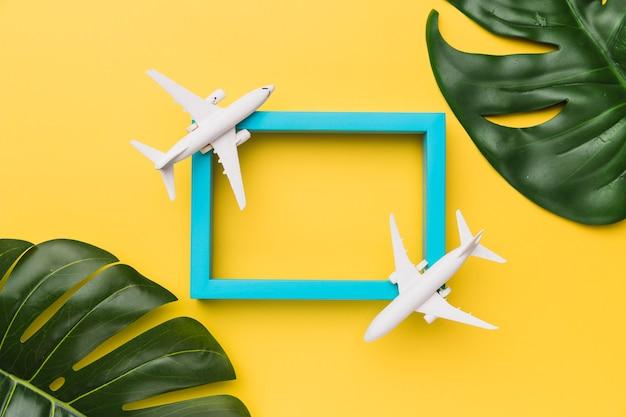 Composición de aviones parados en marco azul y hojas de plantas