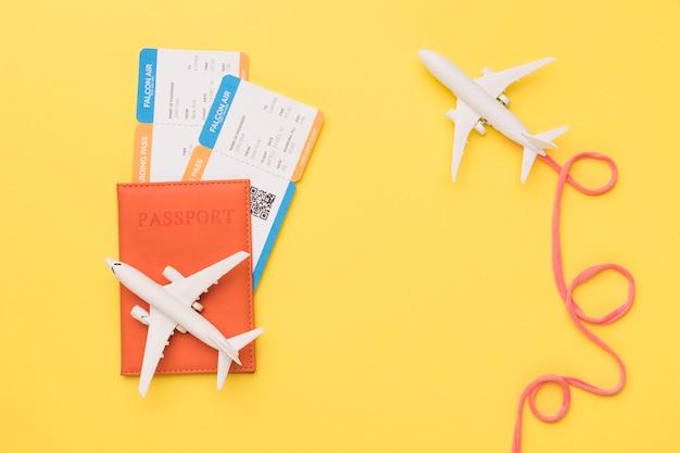 Composición de aviones con pasaporte rosa y boletos de avión.