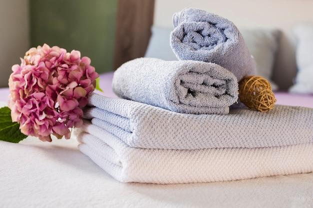 Composición de baño con flores y toallas.