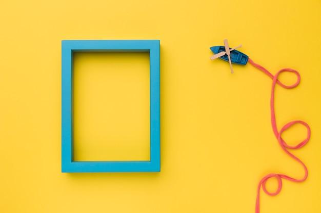 Composición del barco de juguete con estela de popa y marco azul