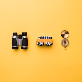 Composición de binoculares bus pequeño juguete y brújula