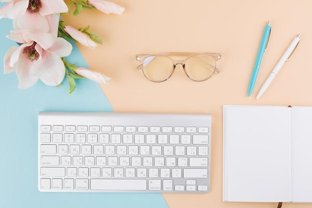 Composición de bloc de notas, teclado, lentes, flores y bolígrafos.