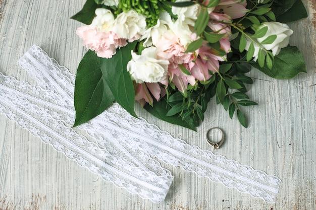 Composición de boda con flores, anillo y silla.