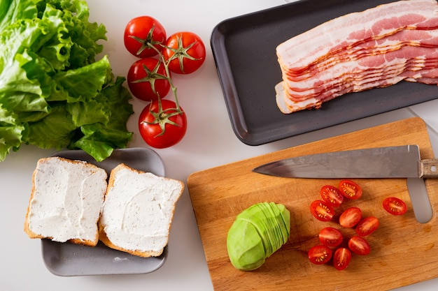Composición de bodegón que consta de dos sándwiches, tomates frescos, lechuga, aguacate y bandeja con rodajas de tocino en la mesa de la cocina