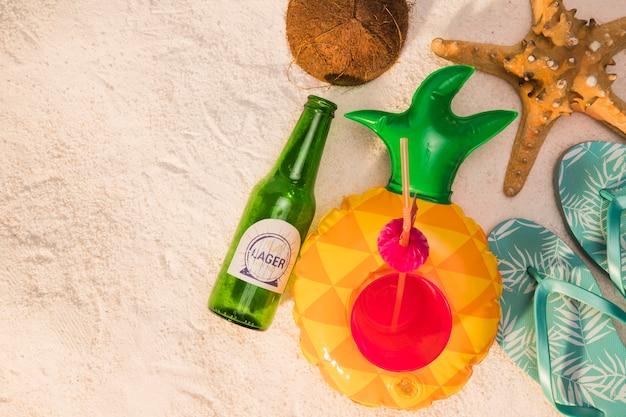 Composición de botella cóctel sandalias estrellas de mar coco en la arena