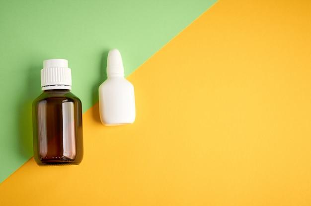 Composición de la botella de spray nasal, botella blanca en blanco sobre fondo amarillo y verde con copyspace
