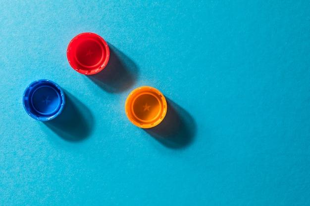 Composición con botellas de plástico y tapas aisladas en azul.