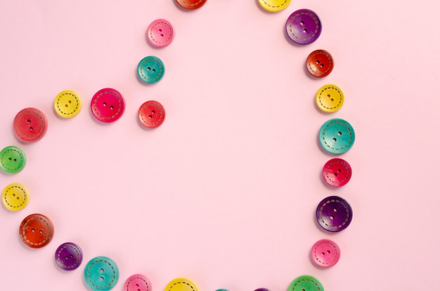 Composición de botones de costura de colores sobre fondo rosa.