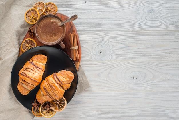 Composición de café y croissants sobre un fondo de madera