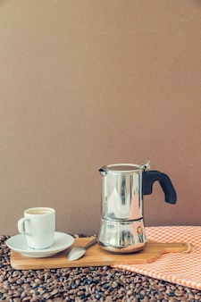 Composición de café con taza y cafetera en tabla de madera